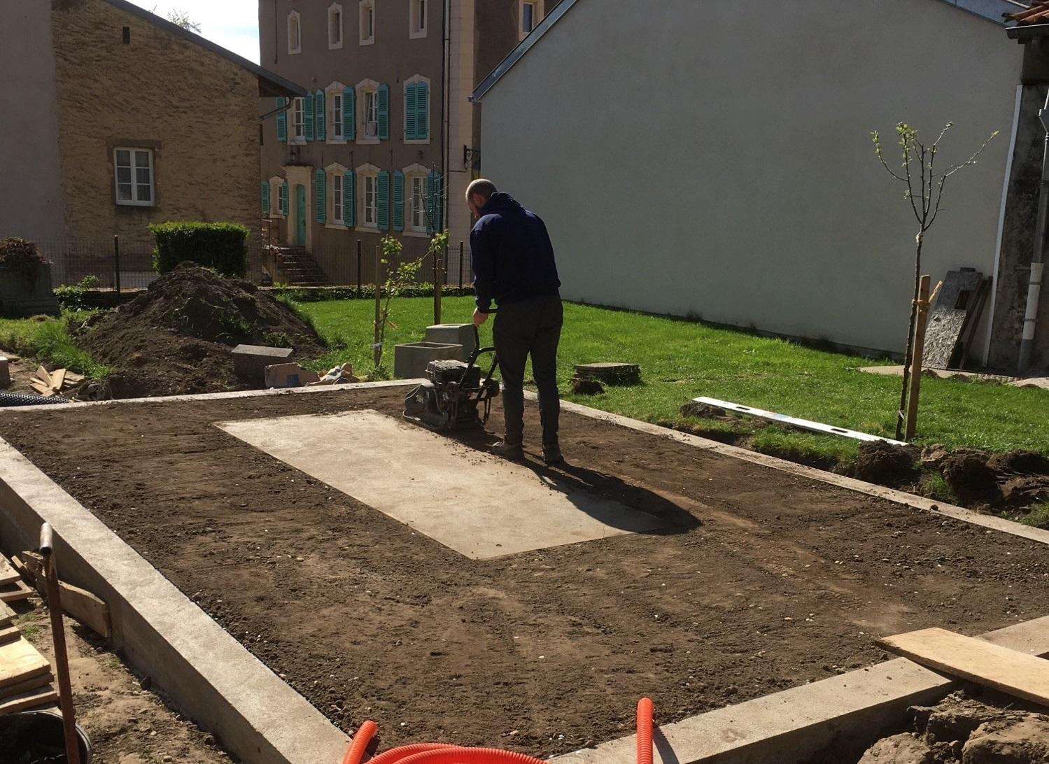 Passage d'une plaque vibrante pour le tassement du sol